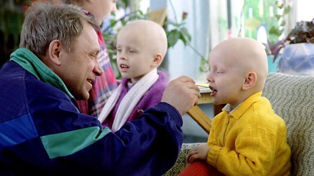 Ein Vater füttert seine Kinder im Krebskrankenhaus von Minsk.