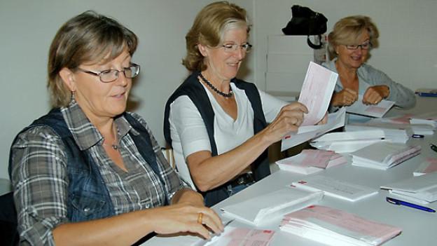 Helferinnen packen Einzahlungsscheine in Couverts.