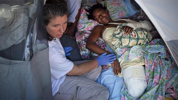 Mitarbeiter von Handicap International betreuen eine am Bein amputierte Haitianerin.