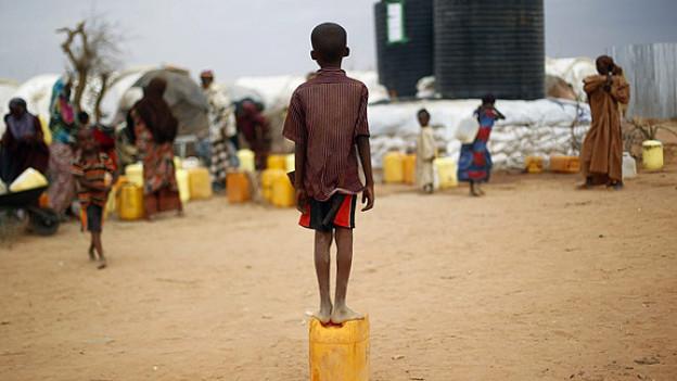 Ausserhalb vom Flüchtlingscamp in Dadaab: Ein Kind aus Somalien wartet darauf, eine Ration Wasser zu erhalten.