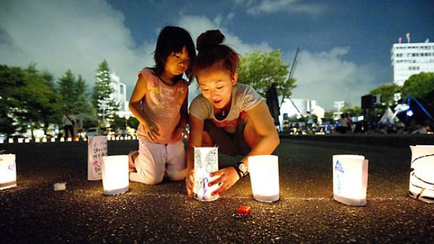 Eine Japanerin zündet mit ihrer Tochter eine Kerze an, zum Gedenken an die Opfer in Japan im März 2011.