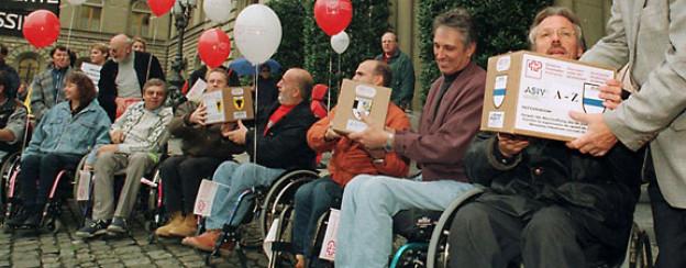 Behinderte übergeben in Bern der Bundeskanzlei über 70'000 Referendumsunterschriften gegen die Abschaffung der 1/4-Rente, Oktober 1998.