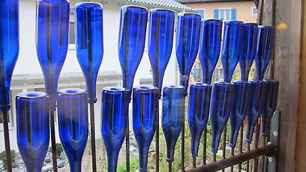 Statt biedere Vorhänge dienen blaue Prosecco-Flaschen als Sichtschutz.