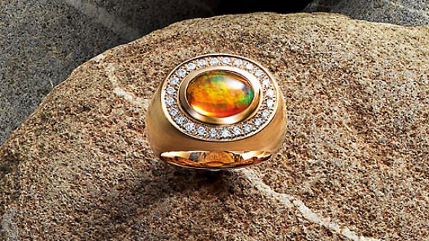 Ring aus Rotgold mit Feueropal und 24 Brillanten.