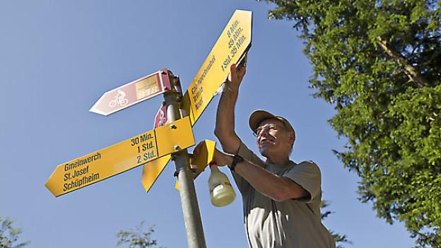 Zur Freiwilligenarbeit gehört auch Wegweiser für Wanderwege putzen.