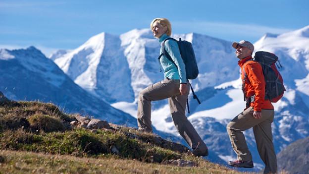 Mann und Frau wandern durch Bergwelt.
