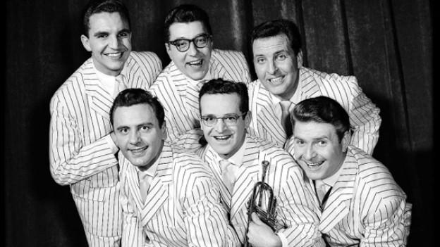 Schwarz-Weiss-Fotografie mit sechs Musikern in weissen Jackets mit feinen grauen Streifen.