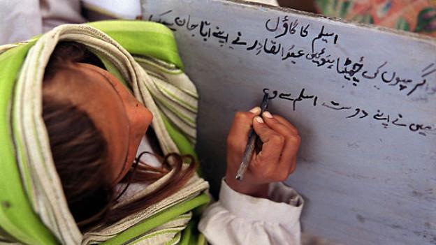 Ein Mädchen lernt schreiben in der Dorfschule in Bhair Sodian, im nordosten Pakistans.