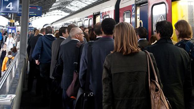 Pendler warten auf ihren Zug beim Bahnhof Lausanne.