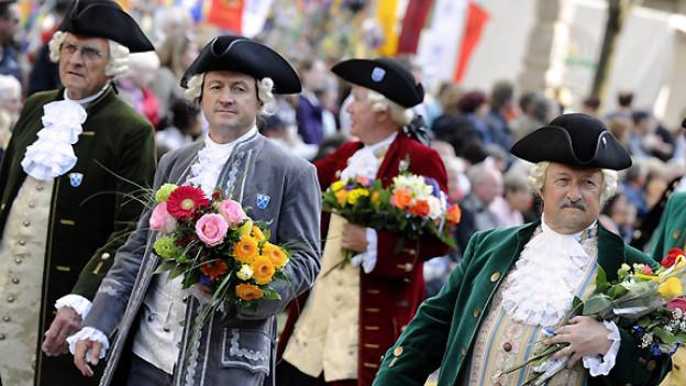 Männer einer Zunft mit ulkigen Perücken und Blumensträussen in der Hand.
