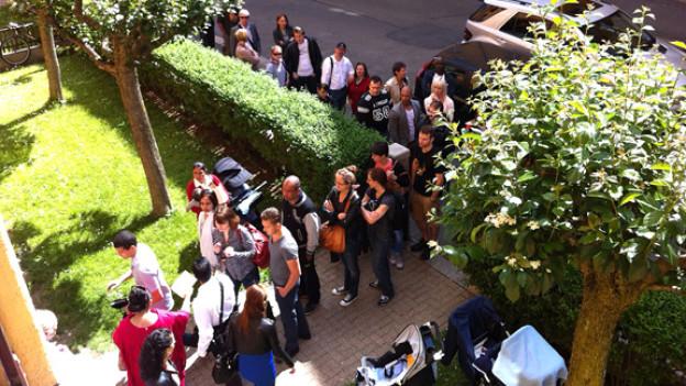 Rund 250 MietinteressentInnen stehen am Montag Vormittag Schlange, um die 2-Zimmerwohnung im Zürcher Kreis 5 anzuschauen.