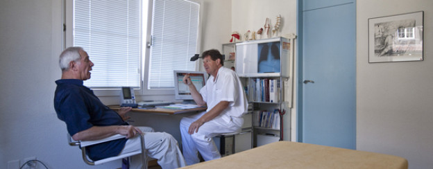 Allgemeinpraktiker Peter Zaech berät einen Patienten mit Rückenschmerzen.