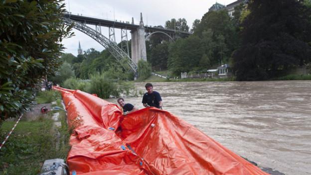 Mitarbeiter der freiwilligen Feuerwehr errichten an der Aare mit Wasser gefuellte Wassersperren.