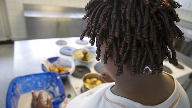 Eine Tongolese Asylbewerberin bereitet das Nachtessen vor im Asylantenheim «Salesheim» in Schwyz.