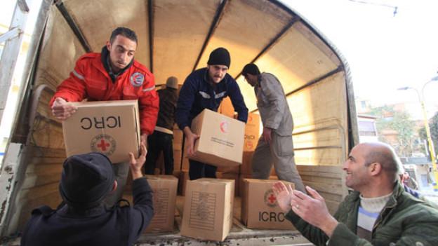 Mitarbeiter des Syrischen Roten Halbmondes beim Verteilen von Hilfsgütern.