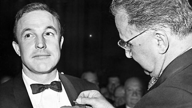 Der Schauspieler Gene Kelly (links) erhält am 7. Juli 1960 in Paris den Orden Kreuz der Ehrenlegion.