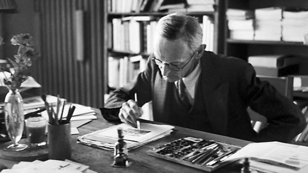 Hermann Hesse arbeitet an einer Illustration in seinem Arbeitszimmer in Montagnola, Tessin.