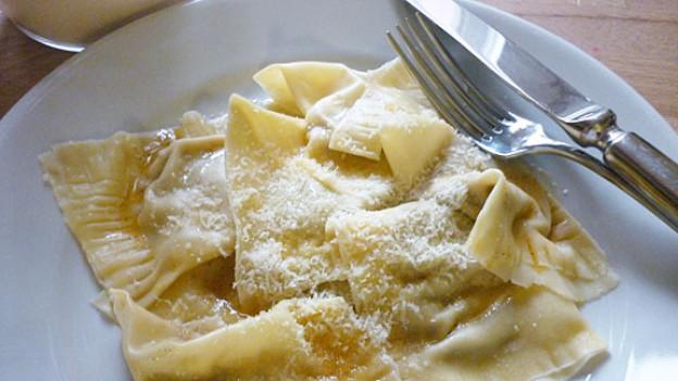Die gekochten Ravioli mit brauner Butter übergiessen und mit Parmesan servieren.