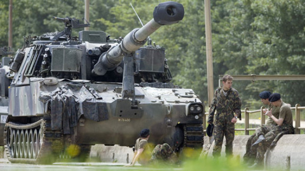 Rekruten der Panzergrenadiere Pz Gren Rekrutenschule ruhen sich nach einer Panzerübung neben einer Panzerhaubitze M109 auf dem Waffenplatz Bure aus, aufgenommen am 18. Juli 2007.