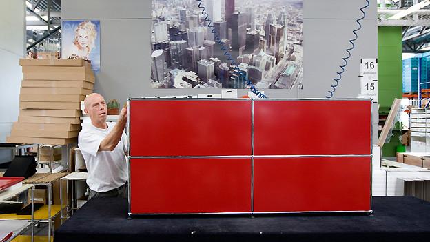 Ein Mitarbeiter des Möbelherstellers USM in Münsingen im Kanton Bern setzt am 8. April 2009 ein Möbelstück der Serie USM Haller zusammen.
