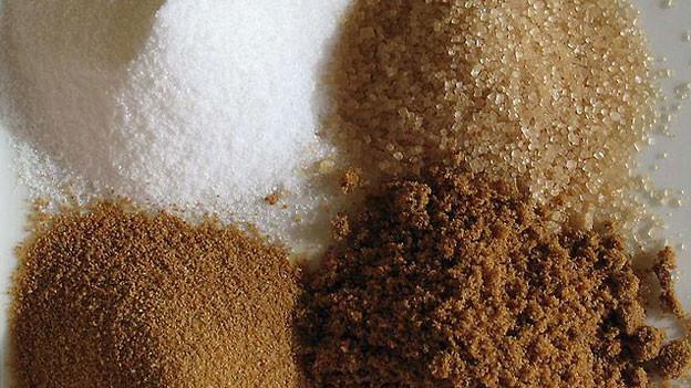 Es gibt verschiedene Sorten von Zucker: Weisser Zucker, Farin-Zucker (oben) und zwei Sorten Vollrohrzucker (unten).
