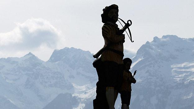 Der Legendaere Wilhelm Tell und sein Sohn Walterli als Statue im Dorfzentrum von Tells Urssprungsort Buergeln.