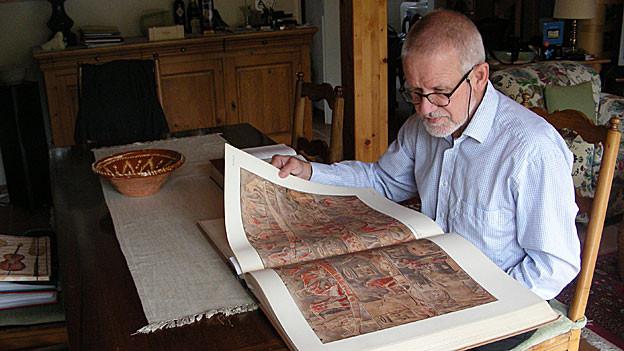 Peter Günther beim Durchblättern des Buchs «The Mastaba of Mereruka».