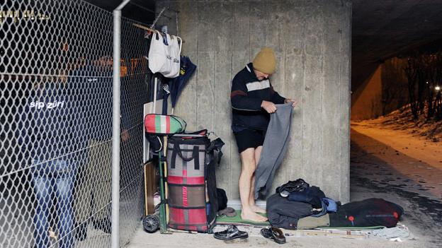 Ein Mann bereitet neben Angehörigen der SIP (Sicherheit, Intervention, Praevention, Stadt Zuerich) seine Schlafstätte unter einer Brücke vor. Obwohl in der Stadt Zürich ein grosses Angebot an Notschlafplätzen besteht, will der Mann nicht umziehen und schläft trotz Minustemperaturen im Februar 2012 draussen.