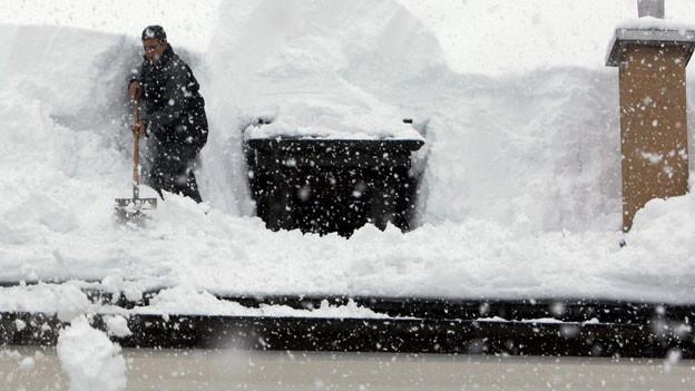 Ein Mann schaufelt 2009 Schnee von einem Hausdach in Airolo.