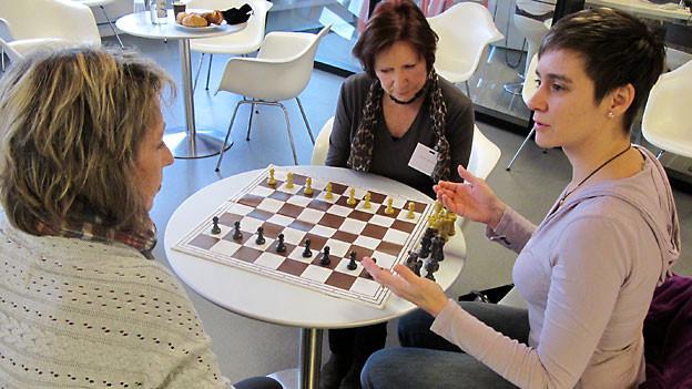 Die beiden Hörerinnen Anita Gaggioli (links) und Margrit Freiermuth (mitte) lernen Schach spielen. Rahel Umbach erklärt die Spielregeln.