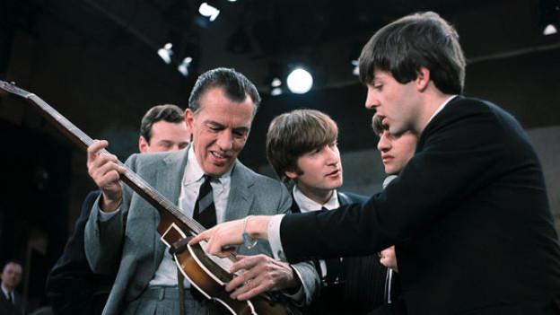 Paul McCartney(rechts) zeigt Ed Sullivan seine Bassgitarre. 1964 hatten die Beatles einen Auftritt in der «Ed Sullivan Show» in New York. Brian Epstein hinten links, war dabei.