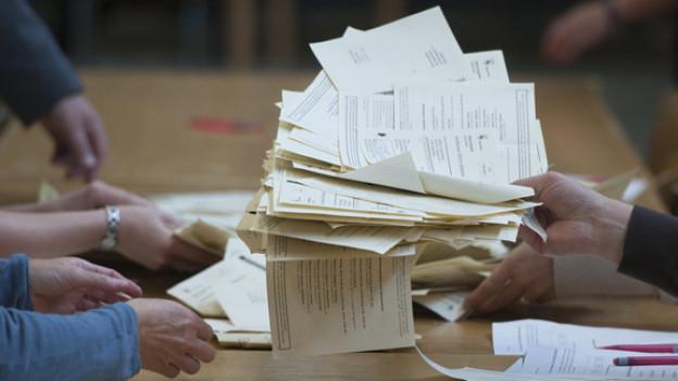 Wahlhelfer kontrollieren die Stimmzettel zu den Parlamentswahlen am Sonntag, 23. Oktober 2011, im Gymnasium Neufeld in Bern.