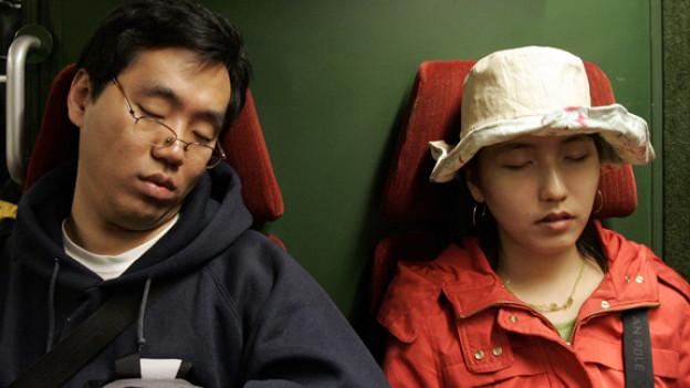 Vom Schlaf übermannte Touristen in der Jungfraujoch-Bahn