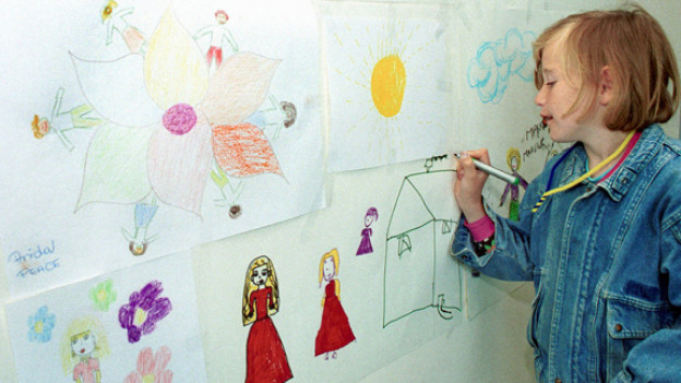Mirela malt in einer Therapiestunde ihre Erfahrungen an die Wand.