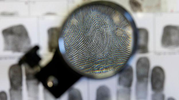 Eine Lupe vergrössert einen Fingerabdruck.