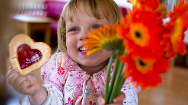 Kind mit Blumenstrauss und Keks in Herzform.