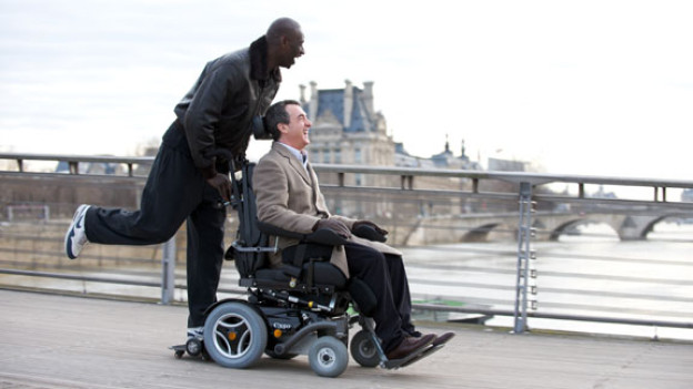 Driss (Omar Sy, links) schraubt an Philippes (François Cluzet) Rollstuhl rum, damit es etwas schneller vorwärts geht.