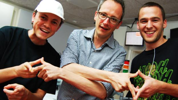 Phenomden, Hannes Hug und Elijah mit dem jamaikanischen «Trinity»-Zeichen für Dreifaltigkeit.