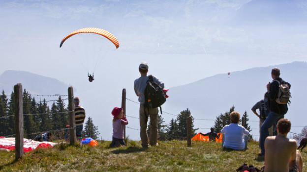 Paraglider starten auf der Rigi und fliegen hinab in Richtung Luzerner See.