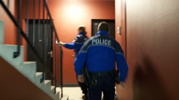 Zwei Lausanner Polizisten bei einer Hausdurchsuchung.