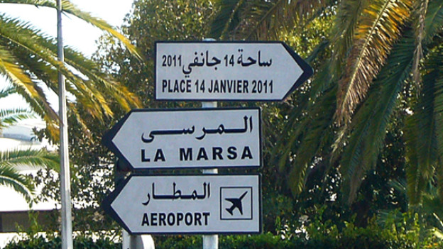 Wegweiser zum «Place 14 Janvier 2011», der auf dem Stadtplan allerdings immer nohc «Place de 7 Novembre 1987» heisst und auf die Zeit vor der Revolution verweist.