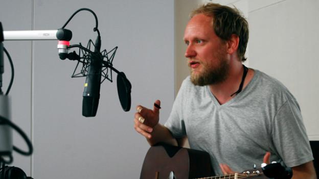 David Philips spielt gleichzeitig Gitarre und Mundharmonika. Unbedingt das Video unten anschauen!