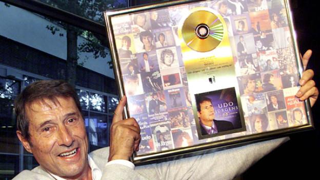 Udo Jürgens hat über 900 Lieder komponiert und 50 Studioalben veröffentlicht. Seine Fans kauften bisher mehr als 100 Millionen Tonträger. Hier wird Jürgens 2001 für sein Livealbum «Mit 66 Jahren» mit der Goldenen Schallplatte ausgezeichnet.
