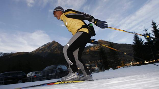 Ein Langläufer startet mit Schwung auf einem schmalen Kunstschneestreifen am Eingang zum schattigen Dischmatal in Davos in die Wintersaison.