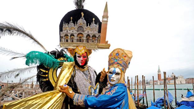 Aufwendige Kostüme vor historischer Kulisse: Karneval in Venedig.