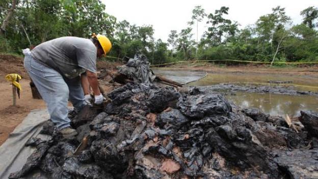 Ein ecuadorianischer Arbeiter beseitigt Ölverschmutzungen.