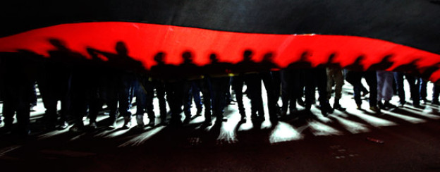 Menschen unter einer riesigen Libyen-Flagge gedenken jenen, die im Kampf gegen Ghadhafi gestorben sind.