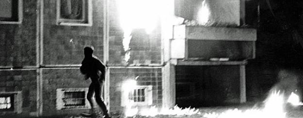 Ein Jugendlicher rennt auf einem Archivbild vom 25. August 1992 an dem brennenden Asylbewerberheim in Rostock-Lichtenhagen vorbei.
