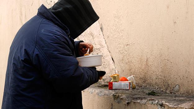 Ein Mann isst Suppe, die täglich auf den Strassen von Athen verteilt wird. Seit der Wirtschaftskrise haben Viele Familien Mühe, über die Runden zu kommen.