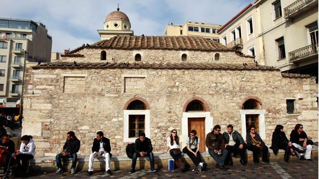 Jugendliche Athener vor einer alten griechisch-orthodoxen Kirche.